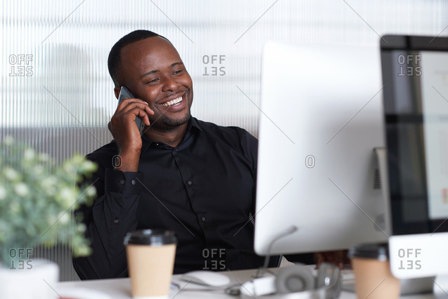 African american businessman using smartphone talking having phone call conversation on mobile in office