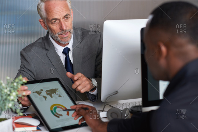 Mature businessman using digital tablet computer showing client financial data pointing at screen meeting in office