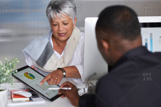 Mature business woman using digital tablet computer showing client financial data pointing at screen meeting in office