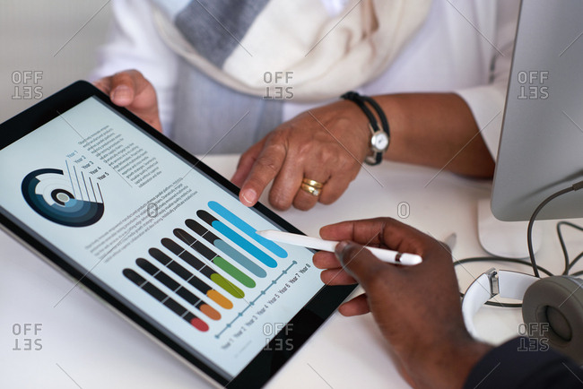 Business people hands using digital tablet computer with financial data on screen meeting in office