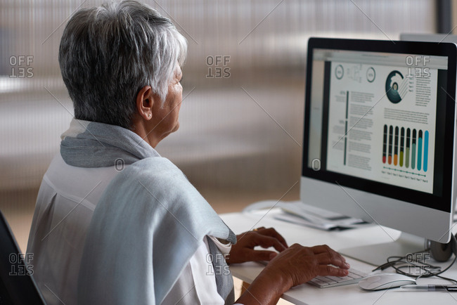 Mature business woman using computer with financial graph data on screen working in office