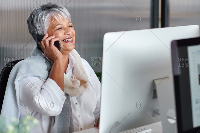 Mature business woman using smartphone chatting having phone call in office by computer