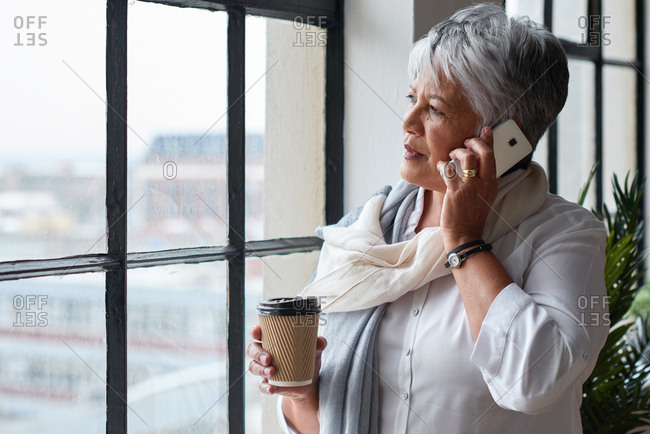 Mature business woman using smartphone having conversation on mobile phone call looking out window in office planning ahead holding coffee