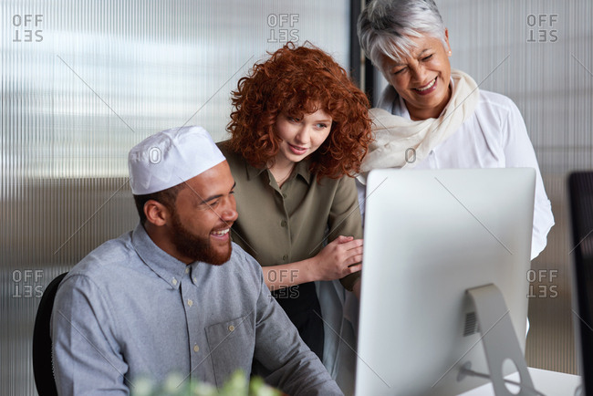 Diverse business people using computer in office meeting