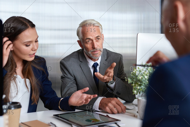 Group of business people meeting in office talking to client with tablet computer on desk