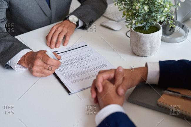 Business people hands signing contract for partnership deal in office meeting