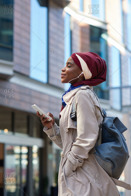 African american business woman using smartphone listening to music with headphones in city independent muslim female wearing headscarf