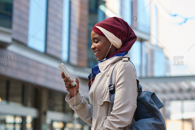 Muslim business woman using smartphone listening to music with headphones in city independent female wearing hijab headscarf