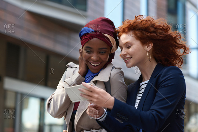 Two business women friends using smartphone looking at mobile phone in city