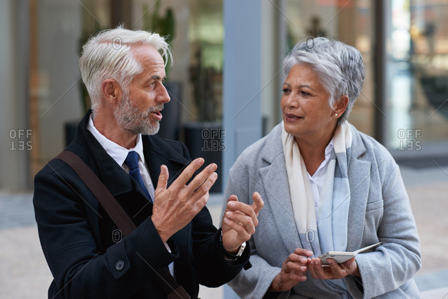Mature business people talking in city senior businessman chatting to partner colleagues having conversation holding smartphones