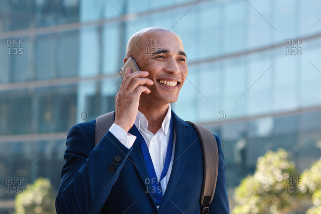 Businessman talking on smartphone having phone call conversation in city