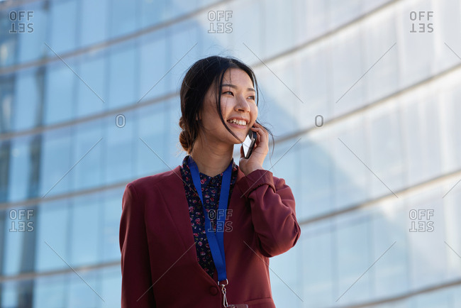 Asian business woman talking using smartphone having phone call conversation in city