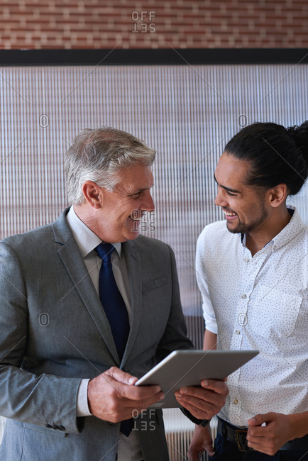 Mature businessman using digital tablet computer discussing information with colleague on touchscreen device in office
