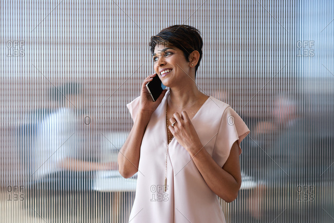 Business woman talking on smartphone having phone call conversation in office