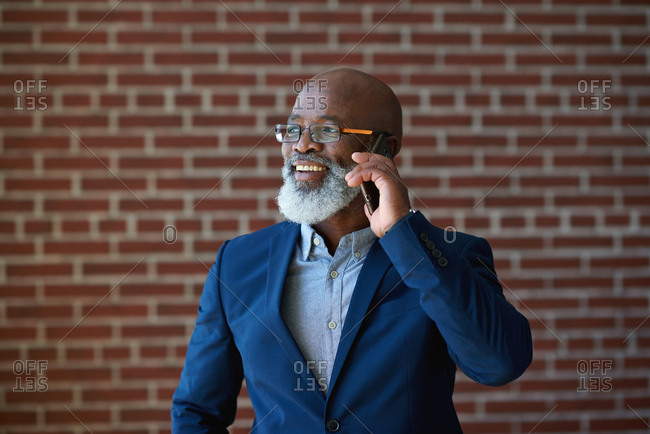 Mature african american businessman using smartphone talking having phone call conversation in office