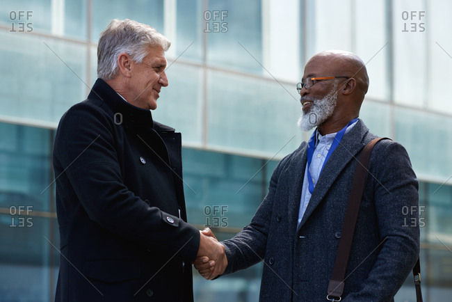 Mature businessmen shaking hands in city with businessman greeting african american client with handshake