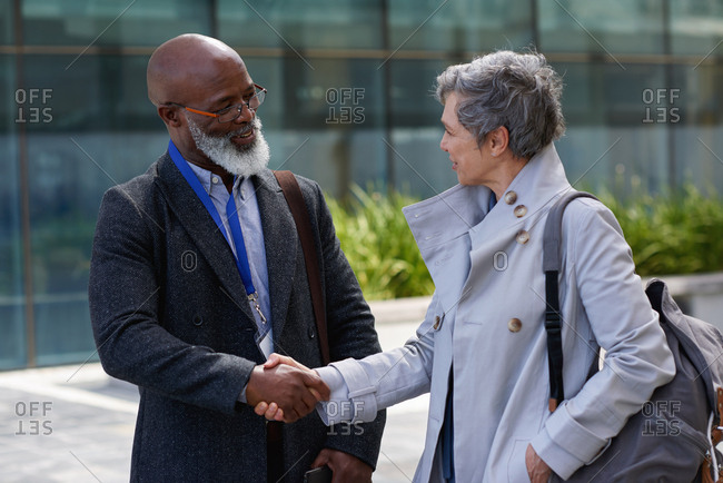 African american businessman shaking hands in city with business woman greeting client with handshake