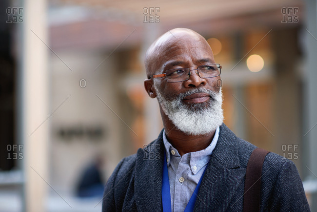 Portrait mature african american businessman looking confident in city wearing glasses