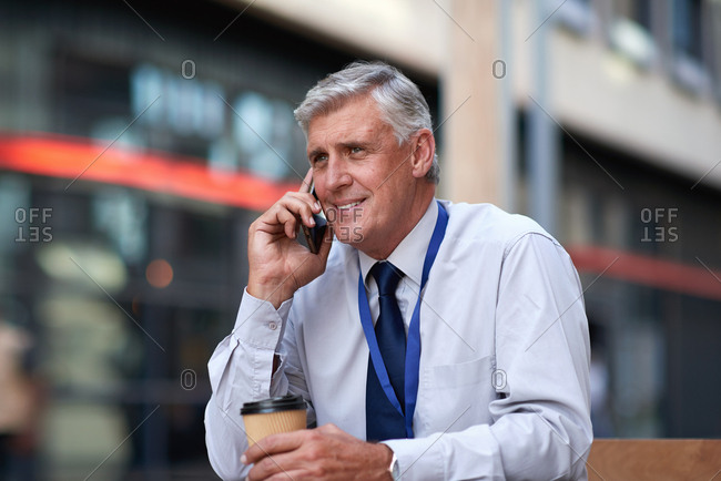 Mature businessman using smartphone talking on mobile phone call having conversation in city smiling happy