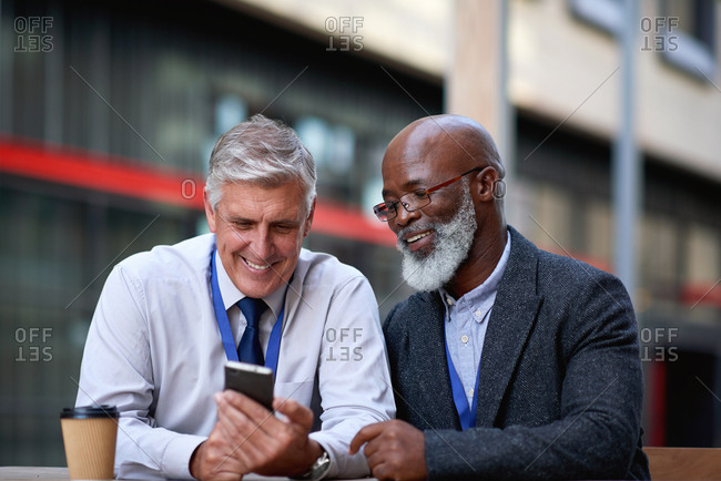 Mature businessmen using smartphone in city businessman looking at mobile phone with friend