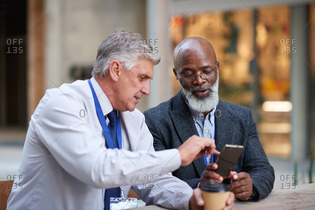Two businessmen using smartphone in city caucasian businessman talking to african american colleague showing mobile phone to friend