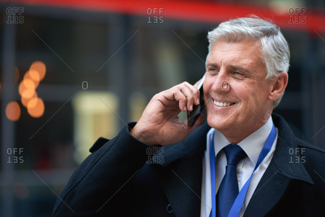 Mature businessman using smartphone talking on mobile phone call having conversation in city