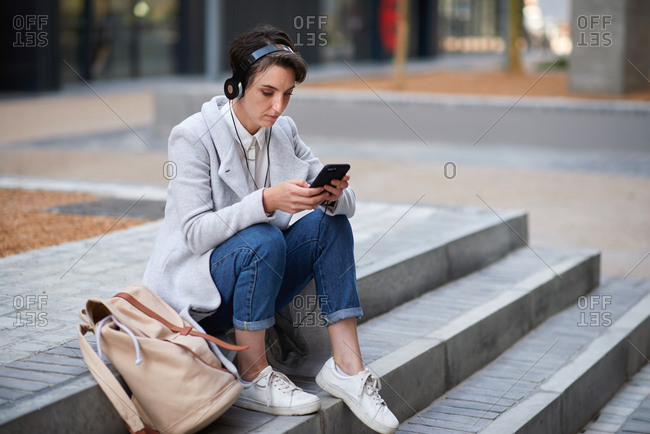 Young business woman using smartphone listening to music wearing headphones texting with mobile phone sitting on steps in city