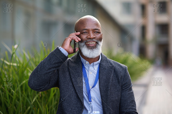 African american businessman using smartphone talking on mobile phone call having conversation in city