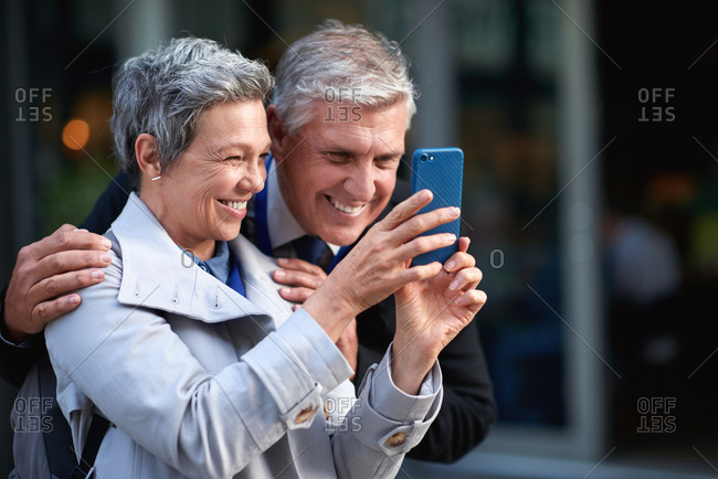 Mature couple taking photo using smartphone in city smiling happy photographing with mobile phone camera