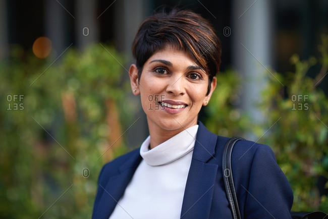 Portrait confident hispanic business woman smiling in city success testimonial