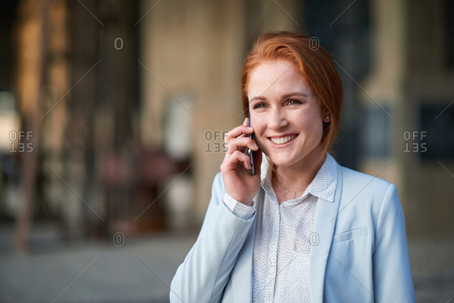 Independent business woman using smartphone talking on mobile phone in city smiling confident female entrepreneur wearing suit