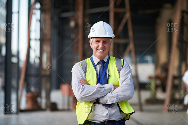 Portrait mature construction worker man smiling confident with arms crossed engineer boss wearing hard hat and reflective vest in city