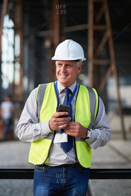 Mature construction worker man using smartphone browsing messages on site wearing hard hat and reflective vest in city