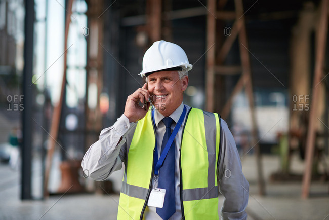 Mature construction worker man using smartphone having phone call conversation on mobile phone wearing hard hat and reflective vest in city