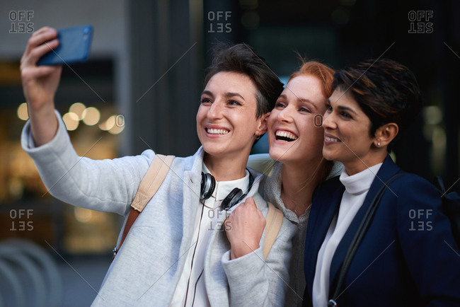 Business women friends taking photo using smartphone in city photographing with mobile phone camera