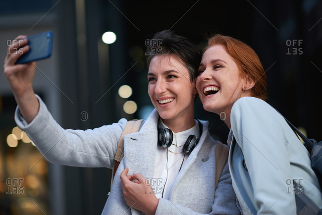 Business women friends taking photo using smartphone in city smiling happy for mobile phone camera