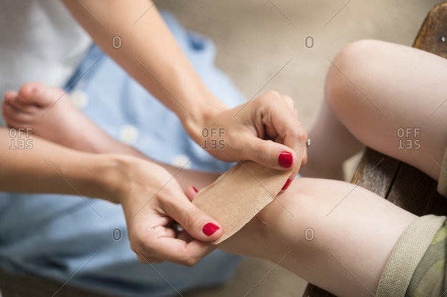 Mother putting bandage on her son's knee