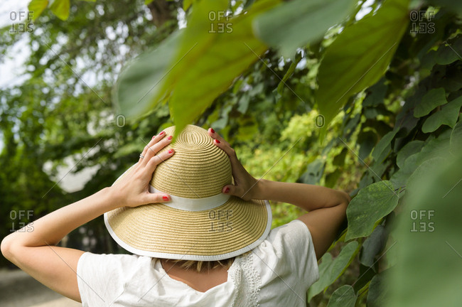 Woman wearing straw hat by trees