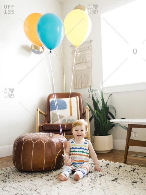 Baby boy holding balloons in living room