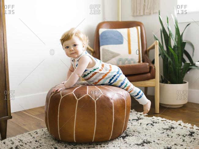 Baby boy lying on ottoman