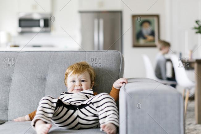Baby boy slumped on sofa