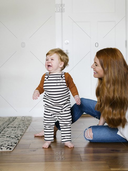 Mother smiling by her crying son