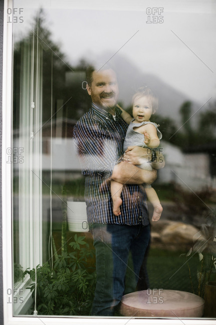 Father holding his daughter behind window