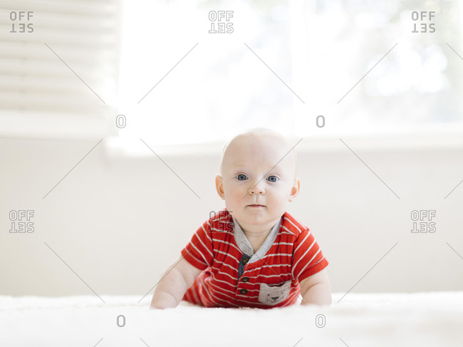 Baby boy wearing striped romper on bed
