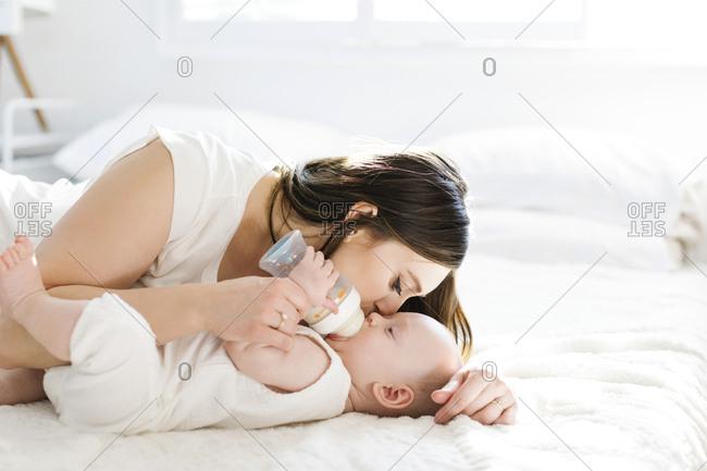 Mother kissing her son's cheek as he drinks bottle of milk