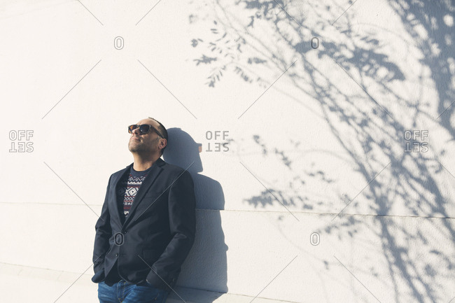 Man wearing sunglasses and blazer by white wall