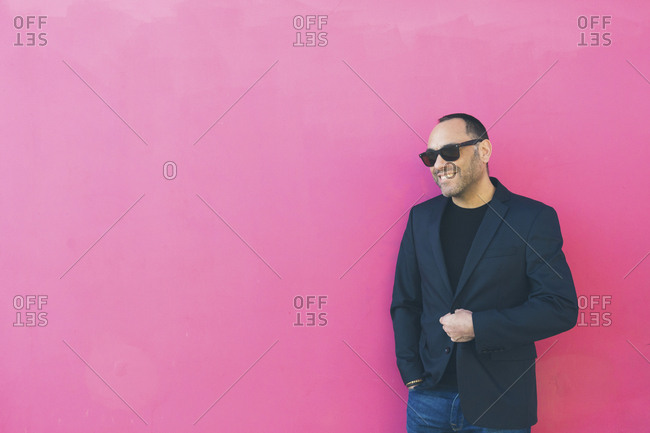 Smiling man wearing sunglasses and blazer by pink wall