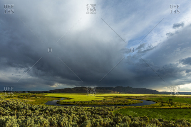 Cloudscape over river through fields in Picabo, Idaho, USA