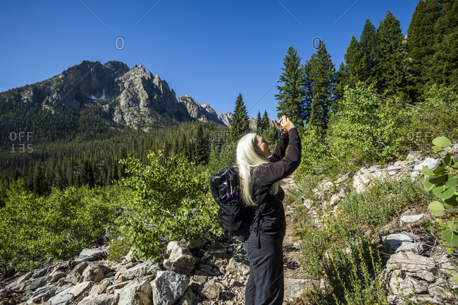 Woman photographing Sawtooth Mountains in Stanley, Idaho, USA