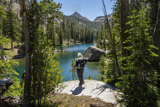 Woman by river in Sawtooth Mountains in Stanley, Idaho, USA